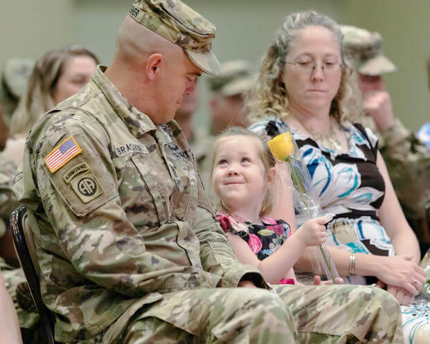 young daughter looking at her father during his change of command