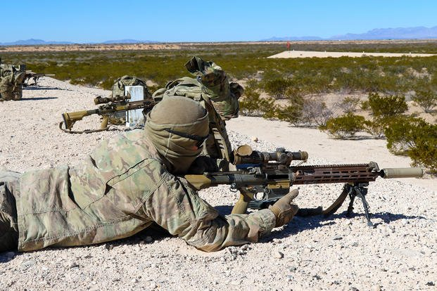 Infantry soldier fires rounds down range with the Squad Designated Marksman Rifle