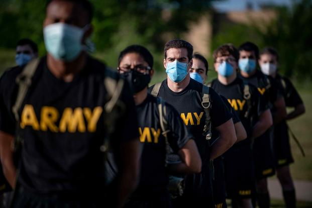 Soldiers stand in formation while wearing masks and maintaining physical distancing.