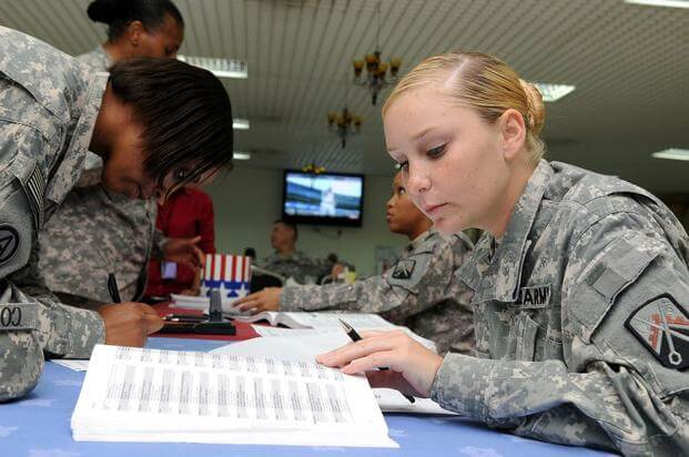 Soldiers fill out their absentee ballot forms at Camp As Sayliyah, Qatar.