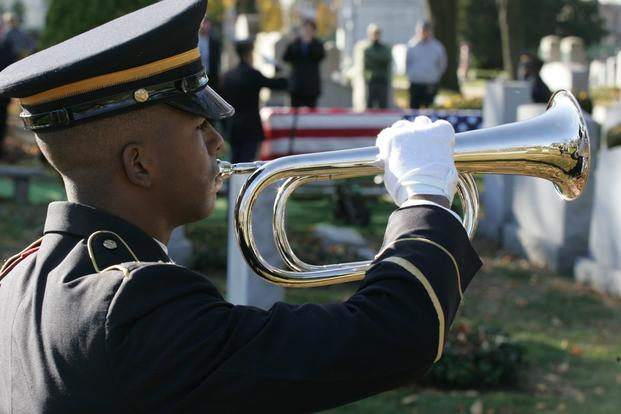 An Army soldier plays taps in the Cypress Hills National Cemetery.