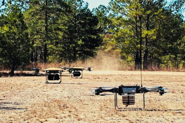 group of quadcopter carrying ammunition and water land in a field to resupply soldiers from the Army's Experimental Force