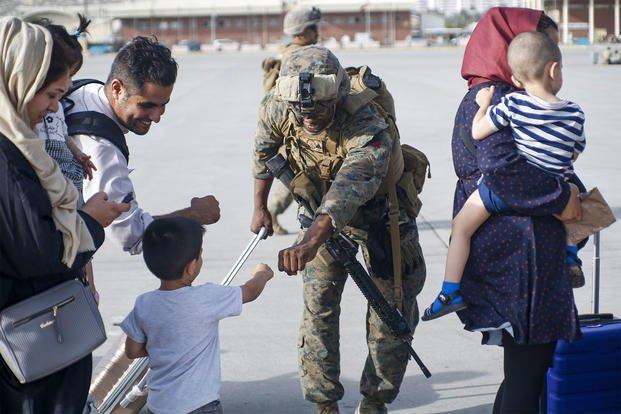 A Marine fists bumps a child evacuee.