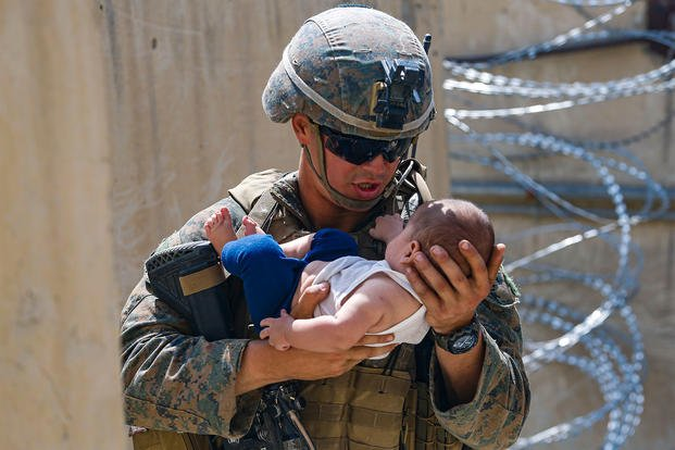 A U.S. Marine assigned to 24th Marine Expeditionary Unit (MEU) comforts an infant.