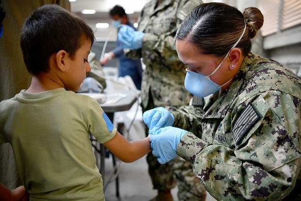 A U.S. Navy Sailor assists an Afghan evacuee.