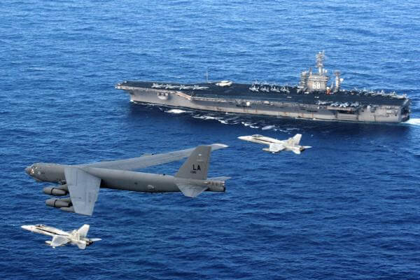 An Air Force B-52 Stratofortress flies past the Navy aircraft carrier USS Nimitz, escorted by two Navy F/A-18 Hornets.  A B-52 recently flew over contested territory in the South China Sea. (U.S. Navy photo)