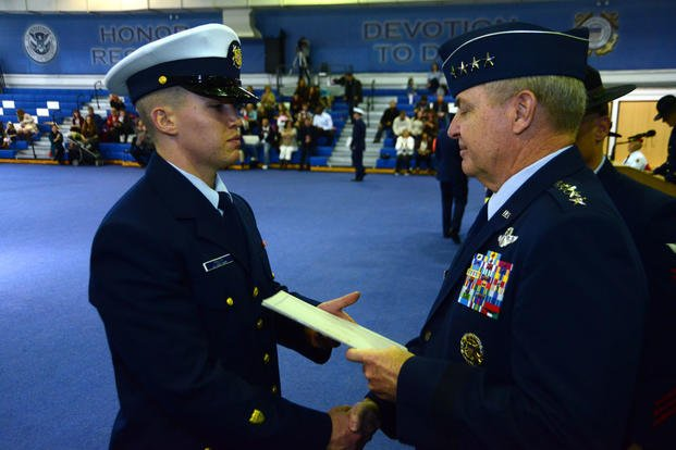 The Chief of Staff of the U.S. Air Force, Gen. Mark A. Welsh III, hands Seaman Patrick Knuth a graduation certificate, Friday, Jan. 29, 2016, at Coast Guard Training Center Cape May, N.J. (Photo: Chief Warrant Officer John Edwards)