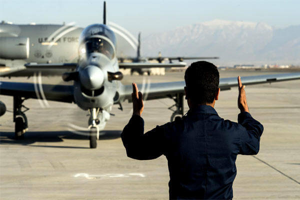 A member of the Afghan Air Force marshals in an A-29 Super Tucano at Hamid Karzai International Airport, Afghanistan, on Jan. 15. (US Air Force/Nathan Lipscomb)