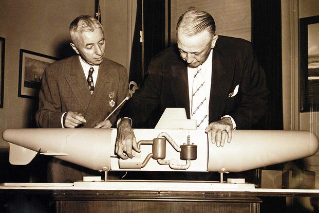 Secretary of the Navy Dan A. Kimball, (right), inspects a model of the Navy's atomic submarine, the Nautilus after presenting Captain Hyman George Rickover, USN, (left), the Gold Star at ceremonies in his office at the Pentagon. (U.S. Navy photo)