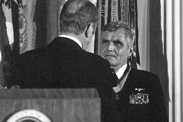 Washington, D.C. (March 4, 1976) - President Gerald R. Ford, (back to camera) presents the Medal of Honor to Rear Admiral James B. Stockdale, USN, during an awards ceremony in the East Room of the White House. (Photo: U.S. Navy)