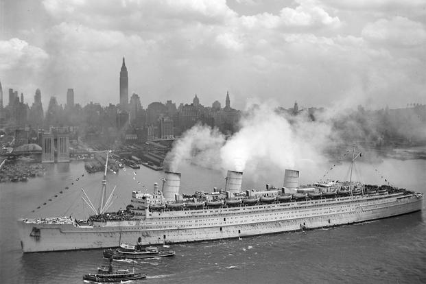 The British liner RMS Queen Mary arrives in New York harbour, 20 June 1945, with thousands of U.S. troops from Europe. The Queen Mary still wears her light grey war paint. Seen from near Hamilton Avenue, Weehawken. 20 June 1945 (Photo: U.S. Navy)