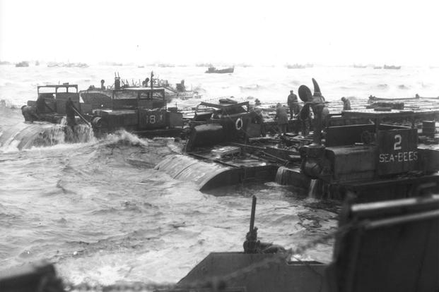 Three Rhino barges and a petrol barge are being hammered by surf somewhere along the coast of France. (Photo: U.S. Army)