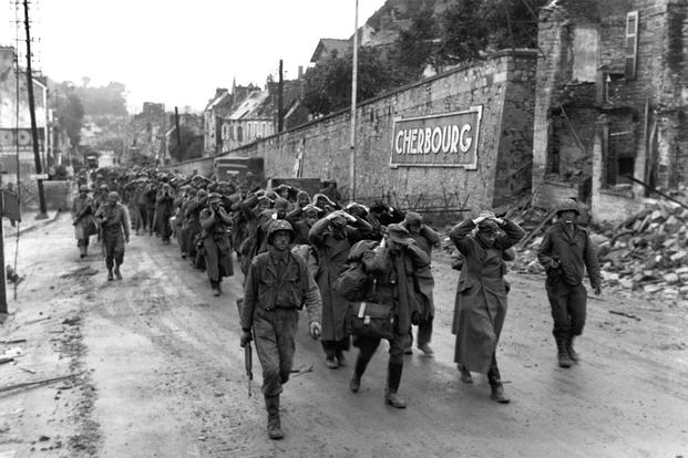 German prisoners march out of surrendered Cherbourg under U.S. Army guard. (U.S. Navy photo)