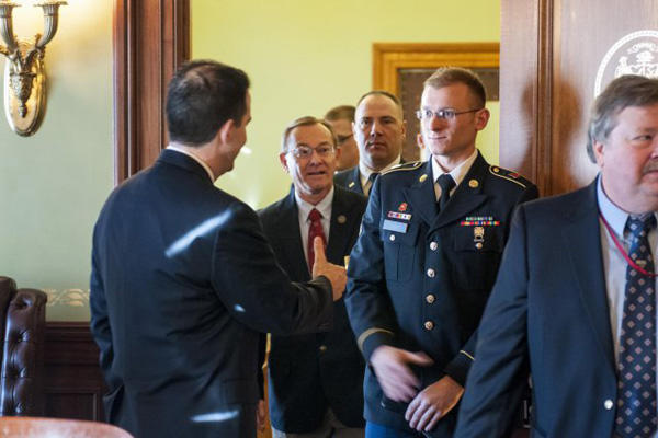 Wisconsin Gov. Scott Walker reaches to shake hands with Spc. Mitchell Fromm