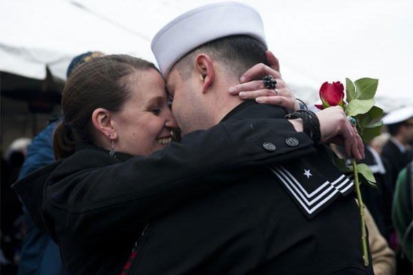 Wife with rose greets sailor.