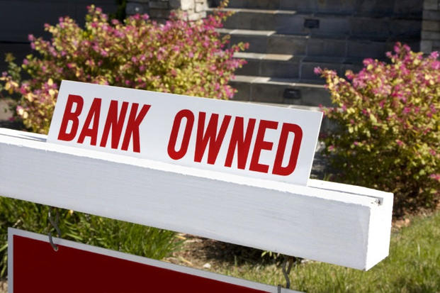 bank owned sign next to house