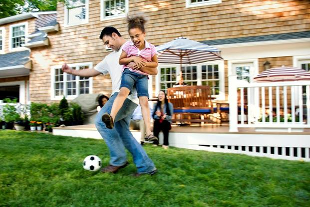 family playing soccer on lawn