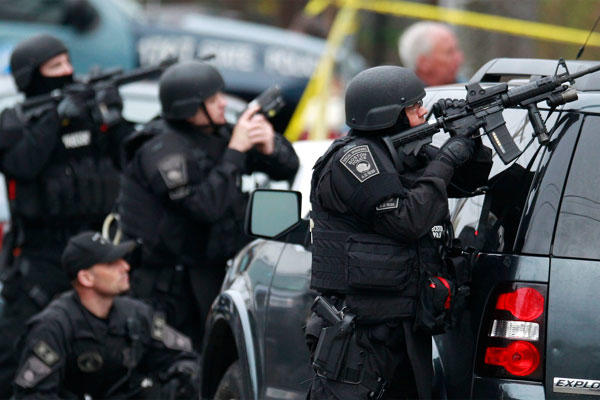 Police in tactical gear surround an apartment building while looking for a suspect in the Boston Marathon bombings in Watertown, Mass., Friday, April 19, 2013.