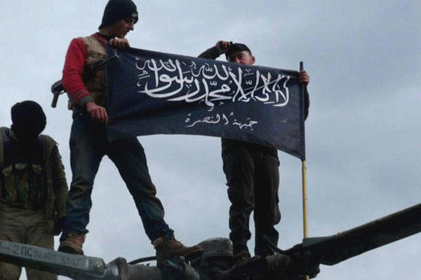Rebels from al-Qaida affiliated Jabhat al-Nusra waving their brigade flag on the top of a Syrian air force helicopter, at Taftanaz air base that was captured by the rebels, in Idlib province, northern Syria.