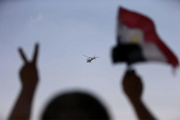 A police helicopter flies over the presidential palace, as a man waves the Egyptian national flag , in Cairo, Egypt, Tuesday, July 2, 2013.