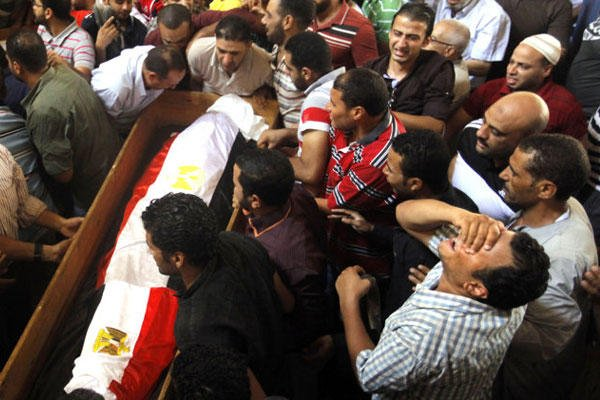 Supporters of Egypt's ousted President Morsi carry a coffin, covered with national flag, of their colleague who was killed during clashes, in Amr Ibn Al-As mosque before funeral prayers in Cairo, Egypt, Friday, Aug. 16, 2013. (AP Photo/Amr Nabil)