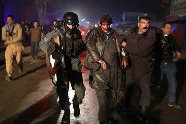 Afghan police forces assist an injured man on Friday, Jan. 17, 2014, at the site where a suicide bomber attacked a Kabul restaurant popular with foreigners. Massoud Hossaini/AP
