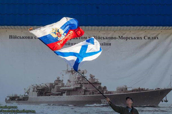 A pro-Russian activist waves the Russian state, upper, and Russian Navy flags outside an entrance to the General Staff Headquarters of the Ukrainian Navy in Sevastopol, Ukraine, Monday, March 3, 2014. (AP Photo/Andrew Lubimov)