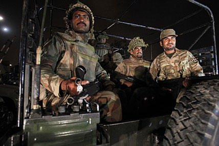 Pakistan army troops arrive at Karachi airport following an attack by unknown gunmen disguised as police guards who stormed a terminal used for VIPs and cargo. (Fareed Khan/Associated Press)