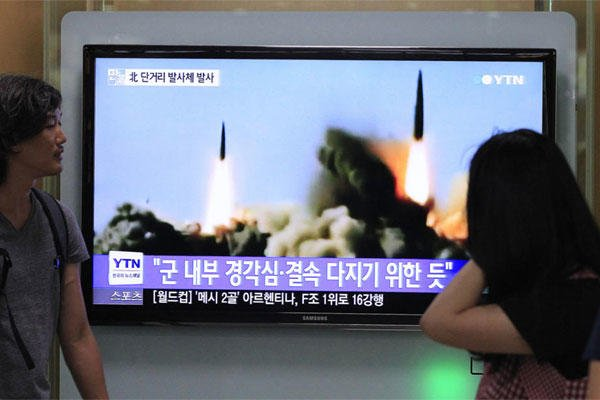 People watch a TV news program showing the missile launch conducted by North Korea, at Seoul Railway Station in Seoul, South Korea, Thursday, June 26, 2014. (AP Photo/Ahn Young-joon)
