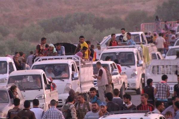 This image made from video taken on Sunday, Aug. 3, 2014 shows Iraqis people from the Yazidi community arriving in Irbil in northern Iraq after Islamic militants attacked the towns of Sinjar and Zunmar. (AP Photo via AP video)