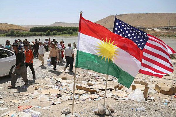 U.S. and Kurdish flags flutter in the wind while displaced Iraqis from the Yazidi community cross the Syria-Iraq border at Feeshkhabour bridge over the Tigris River at Feeshkhabour border point, in northern Iraq, on Aug. 10, 2014. Khalid Mohammed, AP