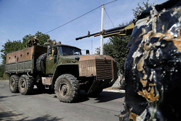 Pro-Russian rebels drive an armored truck in Donetsk, eastern Ukraine, Sunday, Sept. 7, 2014. Sergei Grits/AP