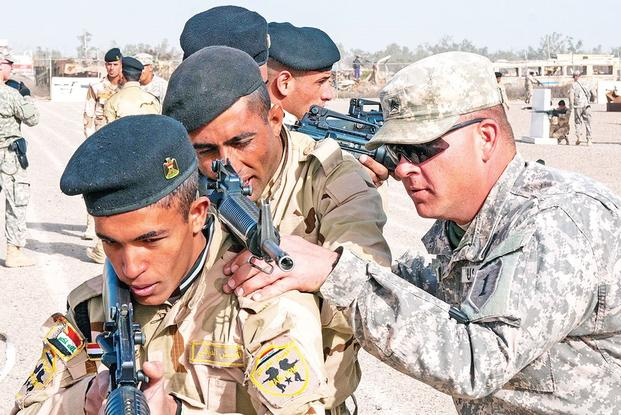 Sgt. David Kappel (right), an infantry trainer assigned to 1st Armored Brigade Combat Team, 1st Infantry Division, adjusts the rifle of an Iraqi army trainee Jan. 7 at Camp Taji, Iraq. (U.S. Army photo)