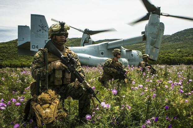 U.S. Marine Lance Cpl. Victor CastilloGarcia, left, a field radio operator from Special-Purpose Marine Air-Ground Task Force Crisis Response-Africa, provides security for an MV-22B Osprey in Spain. (Marine photo)