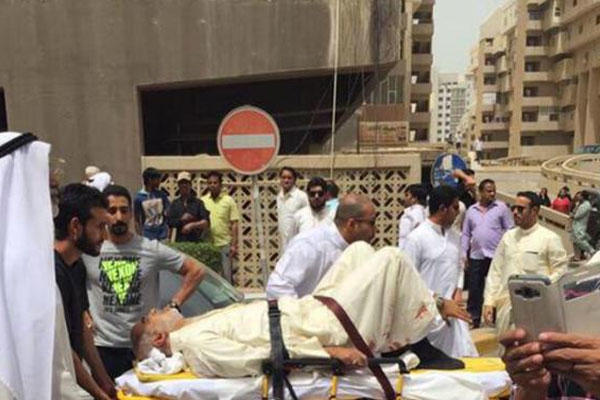 This image provided by Kuwaitna news shows an injured man on a stretcher in the immediate aftermath of a deadly blast at a Shiite mosque in Kuwait City, Friday, June 26, 2015. (Kuwaitna News via AP)