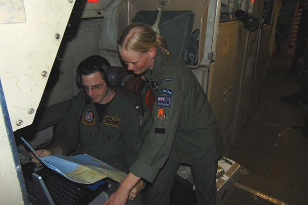 Shane Lewis, with the Golden Swordsmen of Patrol Squadron (VP) 47, examines a chart of New Zealand with an airman from the Royal New Zealand Air Force. (U.S. Navy photo/Lt. j.g Kyle Burdick)