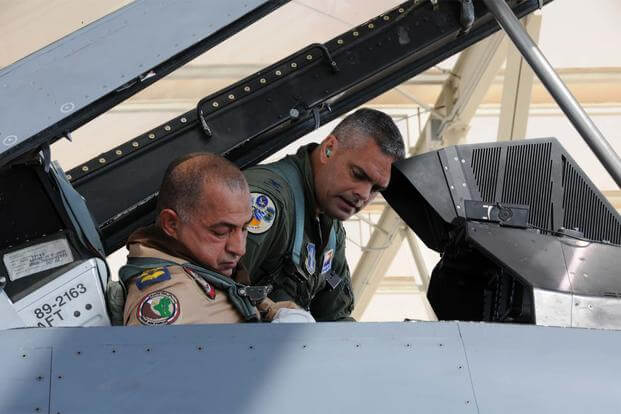 FILE -- Col. Andrew MacDonald helps Iraqi Air Force Brig. Gen. Abdulhussein Lafta Ali Ali buckle into an F-16D Fighting Falcon at Tucson International Airport Aug. 30, 2012 (U.S. Air Force/Maj. Gabe Johnson)