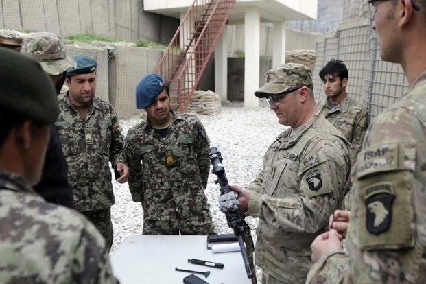 Sgt. 1st Class Chad Clark teaches Afghan National Army soldiers from 4th Combat Support Kandak, 2nd Brigade, 201st Corp, on weapons handling, March 12, 2013, at Combat Outpost Fortress, Kunar Province, Afghanistan. (Photo Credit: Sgt. Jon Heinrich)