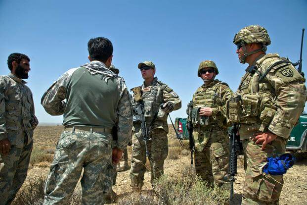 U.S. Air Force Capt. Matthew Zahler and Maj. Jason Helton, air mobility liaison officers, use a translator to talk to Afghanistan border police. (U.S. Air Force/Master Sgt. Jeffrey Allen)
