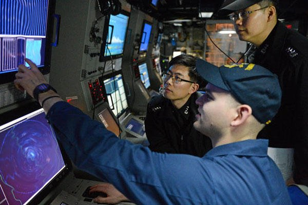 Sonar Technician (Surface) 1st Class Andrew Murphy, foreground, works with South Korean Navy line officers in the sonar control room of the Arleigh Burke-class guided-missile destroyer USS McCampbell during an anti-submarine warfare exercise.