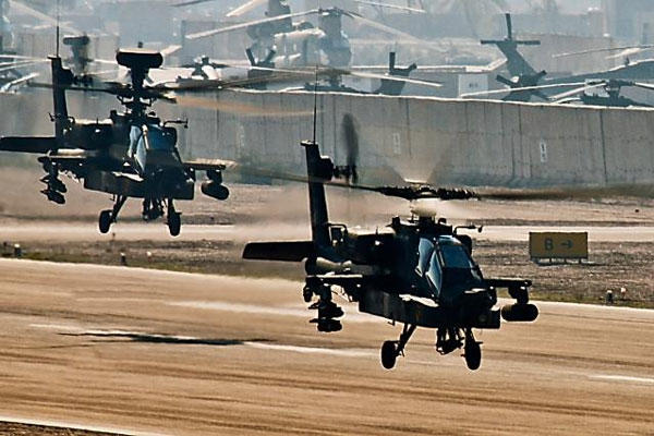 AH-64D Apache attack helicopters from Company C, 4th Battalion, 227th Aviation Regiment, 1st Air Cavalry Brigade, 1st Cavalry Division, depart from the flightline at Camp Taji, Iraq in 2009.