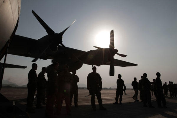 Afghan National Army and International Security Assistance Force personnel gather near a C-130 transport aircraft during a handover ceremony at the Afghan Air Force Base in Kabul, Afghanistan, Wednesday, Oct. 9, 2013.