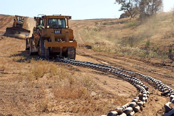 A V8T Dozer drags a chain across a firebreak to flatten its surface as another dozer clears brush from the path, aboard Camp Pendleton, Calif., May 13, 2014.