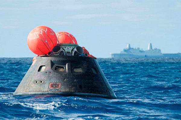 This Dec. 5, 2014 image provided by NASA shows NASA's Orion spacecraft after splash down as it awaits the U.S. Navy's USS Anchorage in the Pacific ocean. (AP Photo/NASA)