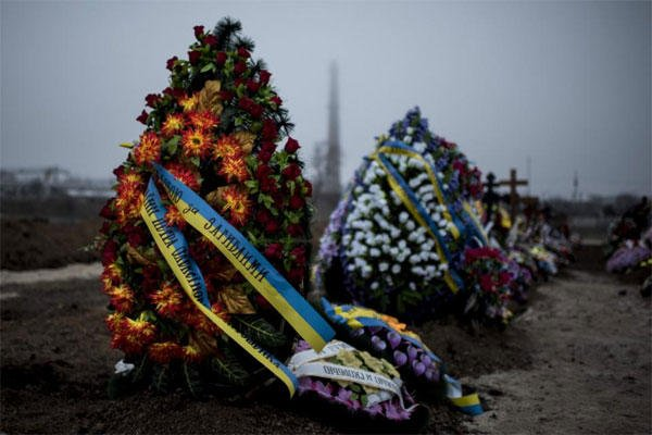Wreaths are placed on the graves of victims of Saturday's shelling after a funeral in Mariupol, Ukraine, Tuesday Jan. 27, 2015. (AP Photo/Evgeniy Maloletka)
