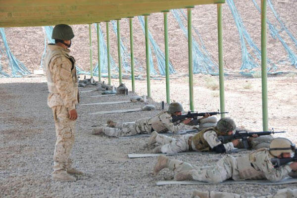 Iraqi Sgt. Mustafa watches as instructors from the Camp Taji Noncommissioned Officer Academy fire while qualifying with M-16 Rifles. (Photo Credit: Sgt. 1st Class Raymond Piper)