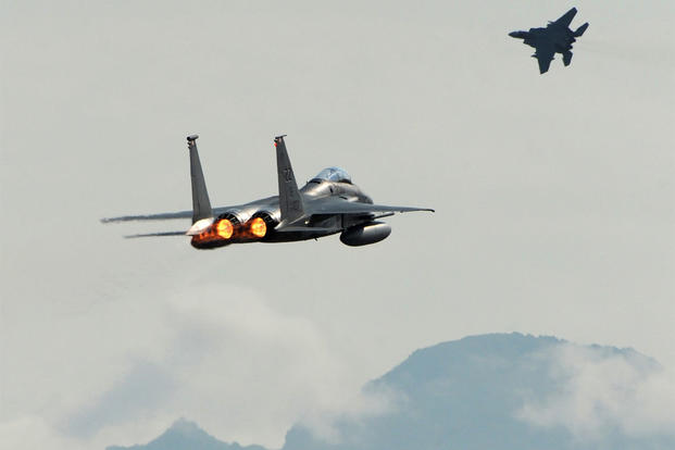 A pair of F-15C Eagles from the 18th Wing at Kadena Air Base, in Japan, take off from Joint Base Elmendorf-Richardson near Anchorage, Alaska, June 23, 2015, while participating in Northern Edge. (Bill Roth/Alaska Dispatch News via AP)
