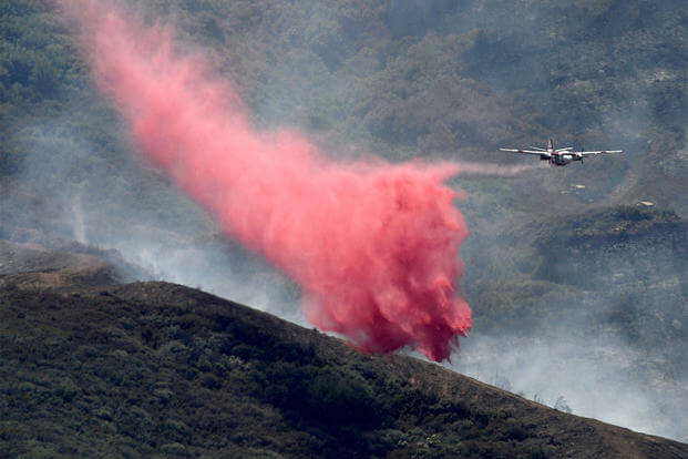 An air tanker makes a retardant drop on a wildfire Wednesday, July 29, 2015, in rural Solano County, Calif.  (Joel Rosenbaum/The Vacaville Reporter via AP)