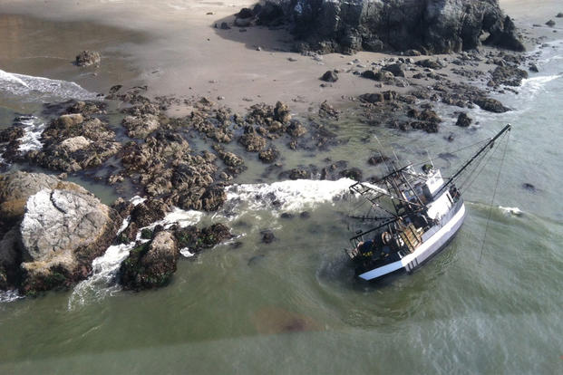 A 52-foot commercial fishing vessel sits aground near Cape Blanco, Ore., July 21, 2015. Coast Guard Petty Officer 2nd Class Darren Harrity pulled all four fishermen aboard to safety through 5-foot seas and 30-mph winds. (U.S. Coast Guard photo)