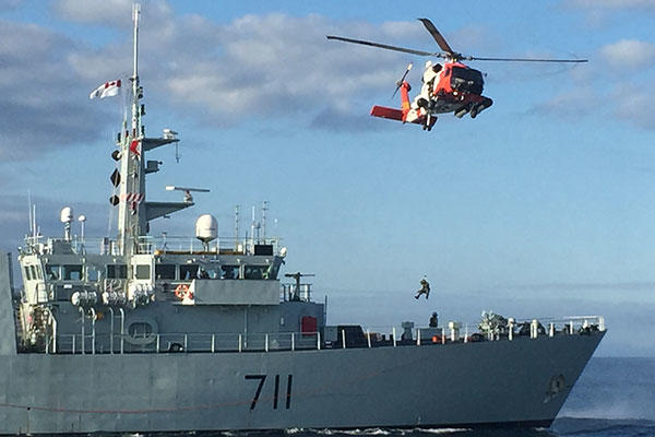 An aviation survival technician and a public affairs specialist were lowered onto the Canadian Warship HMCS Summerside for a mock medical evacuation. (U.S. Coast Guard)